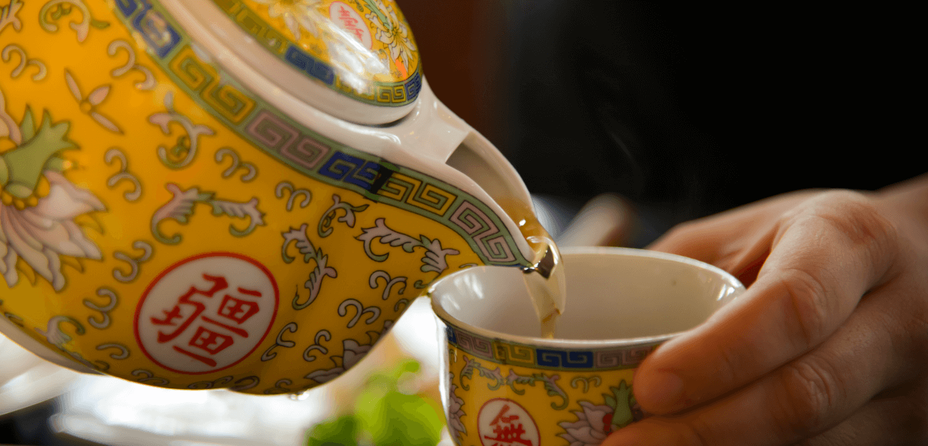 a well designed tea pot pouring tea into a cup