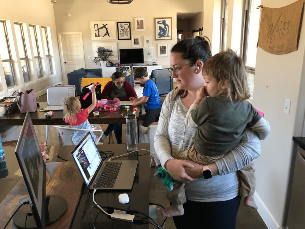 Lindsey holding a baby, while on a work call with kids in the background