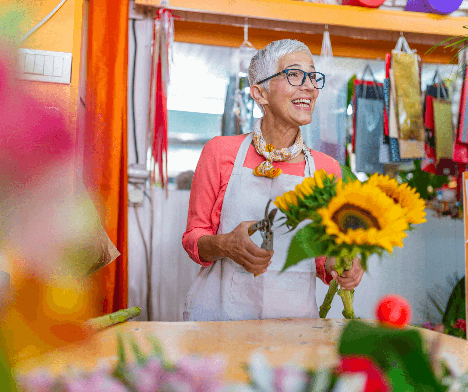 A woman with glasses and short white hair stands in a flower shop holding sunflowers that she is going to clip with scissors she is holding