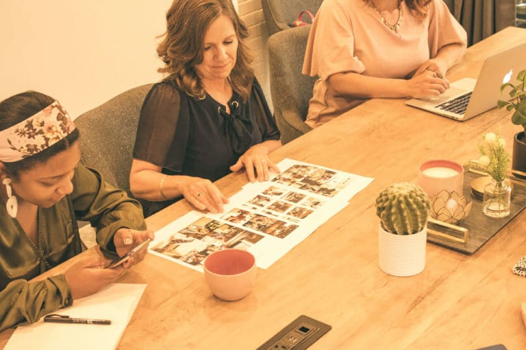 Three women sit at a long table, looking at mood boards while talking