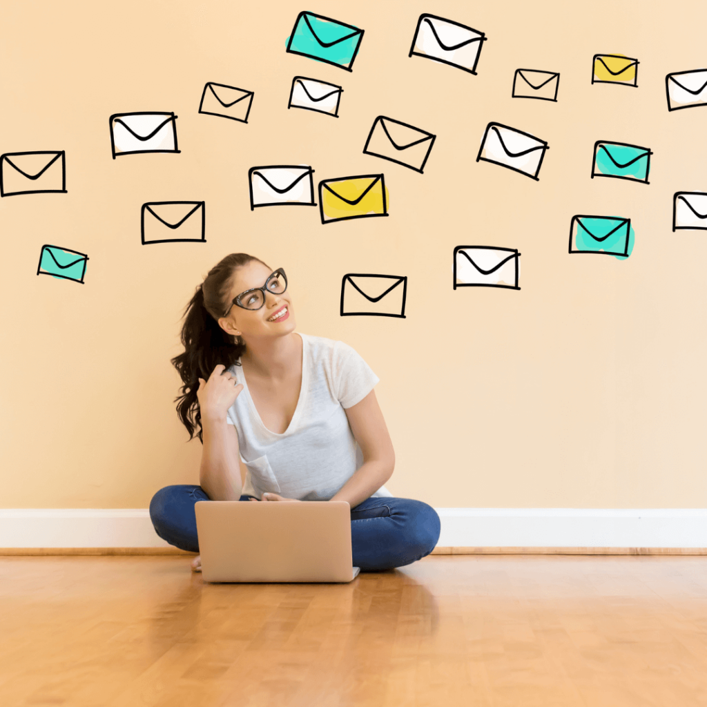 woman with a laptop looking at envelopes floating around her head