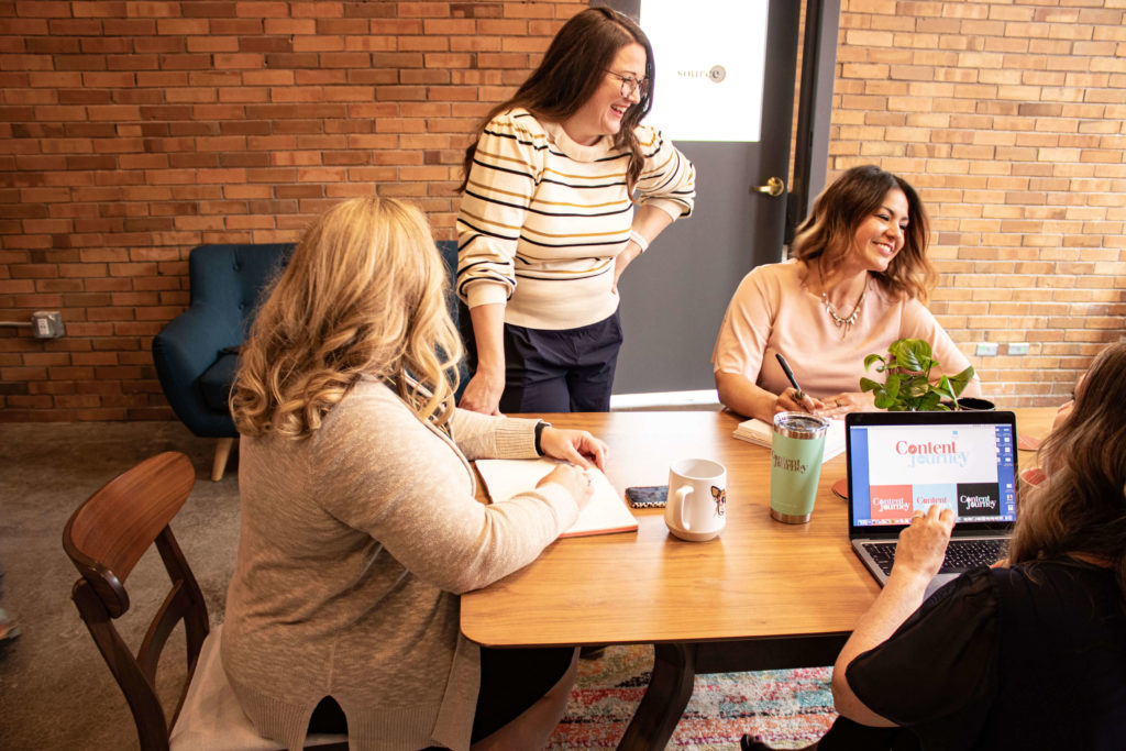 four women at a table working, three are sitting and one is standing