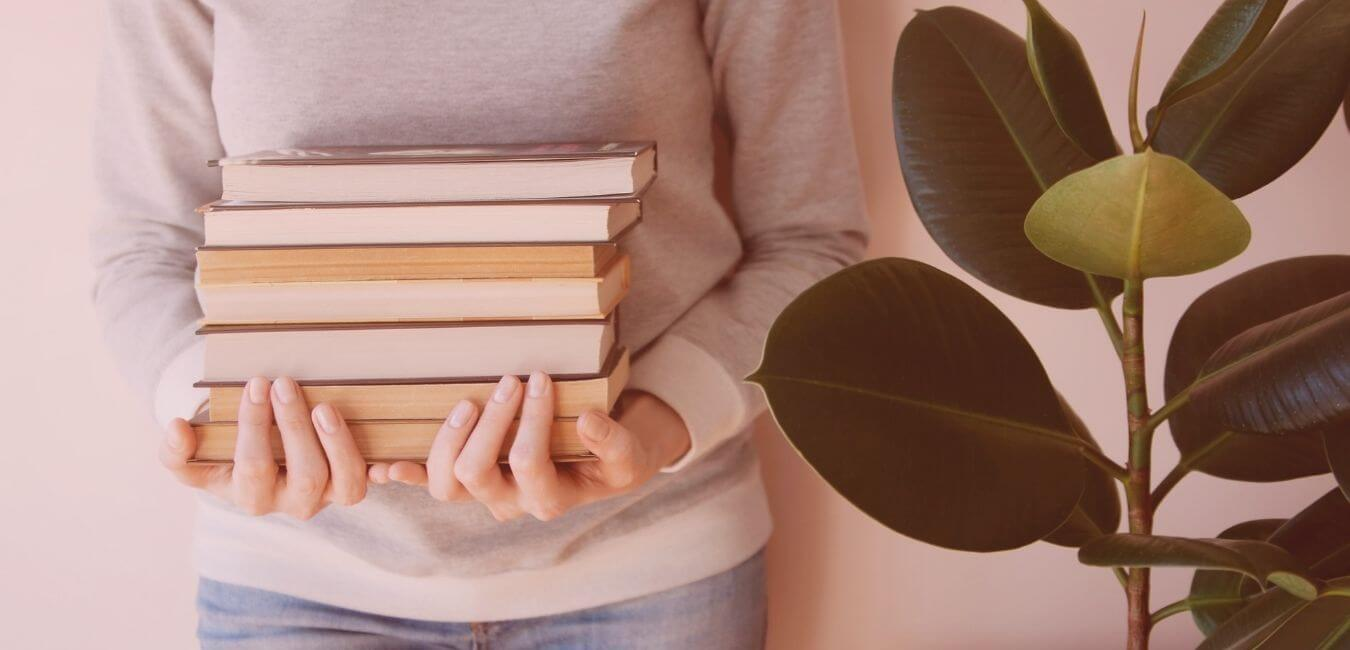 Person holding a pile of books next to a pot plant