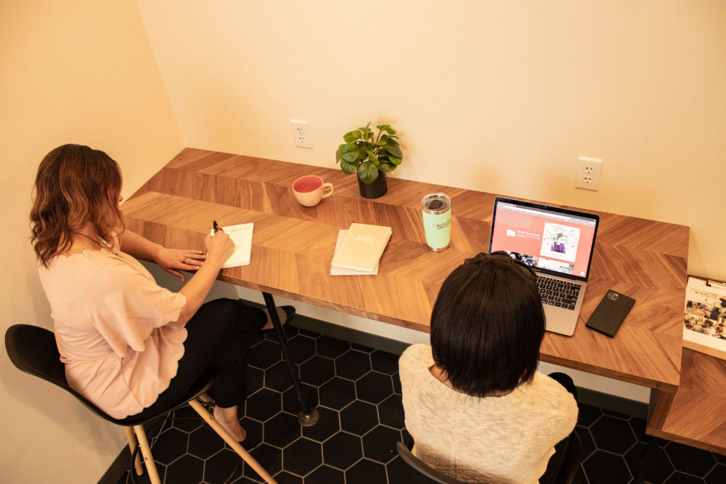 Two women sit at a long table against a wall. One is writing in a notebook the other is on a computer. Their backs are to the camera