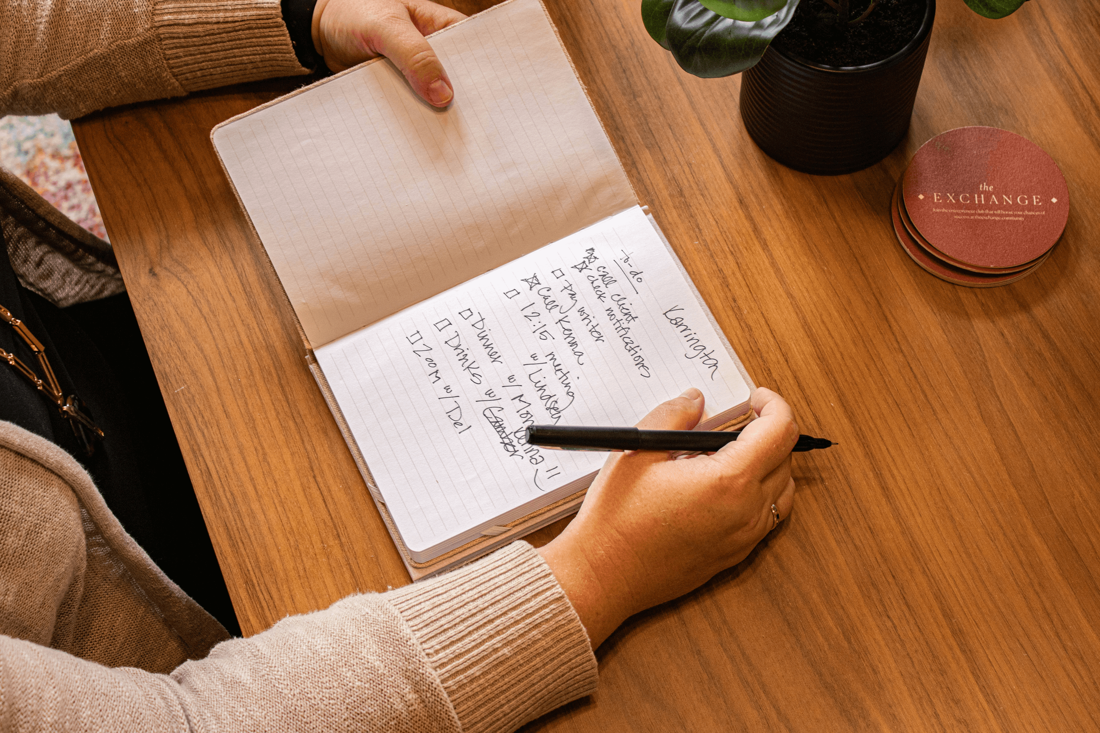 A white female is making a list in a notebook. Only her hands and arms are visible
