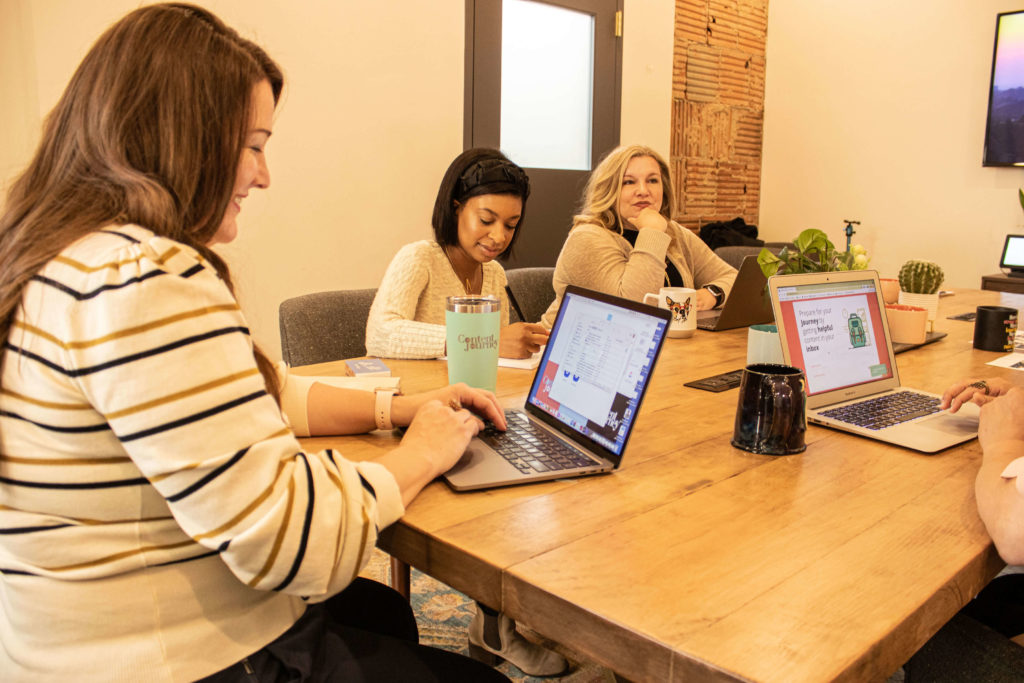 Three women sit at a long table, computers and coffee mugs are on the table top.