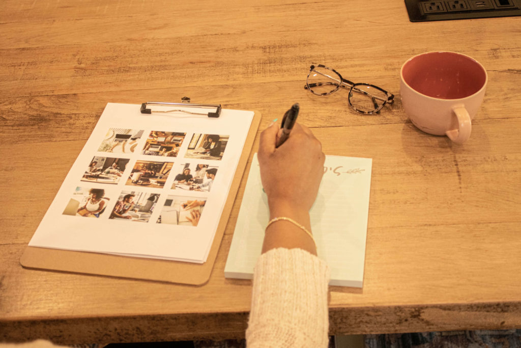 Only the right hand of a woman shows, but she is holding a pen writing on a pad of paper on a desk, with glasses and a coffee mug on the corner