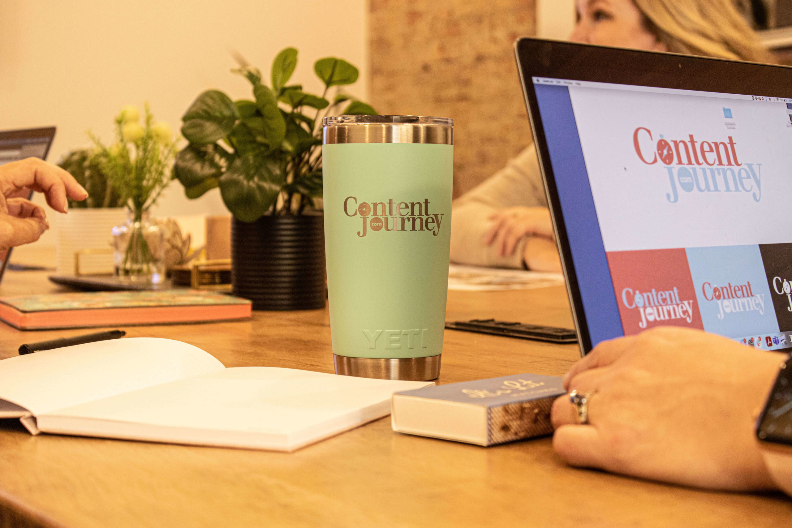A computer and a coffee mug sit on a table where women are working, the logo for Content Journey is displayed