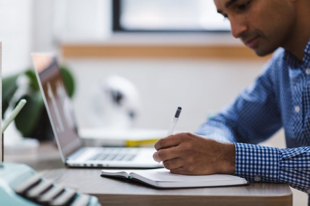 Man writing on a notepad while his laptop sits in the background.