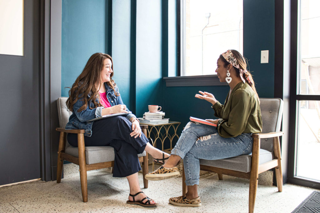 A woman telling a story to another woman while they sit in a lobby.