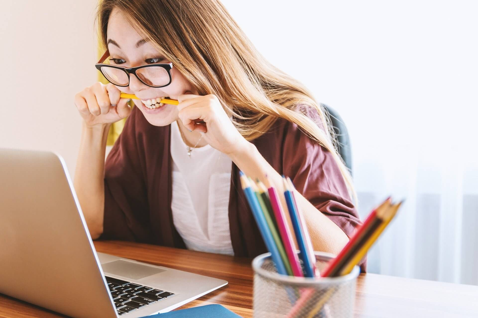 A frustrated woman, biting a pencil while staring at her laptop.